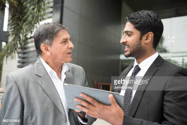 Two businessmen with digital tablet outside modern building