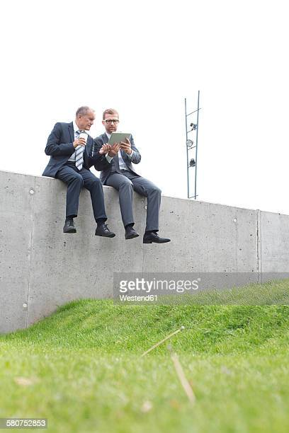 Two businessmen with digital tablet sitting on concrete wall