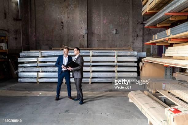two businessmen with folder talking in an old storehouse - finanzen und wirtschaft stock-fotos und bilder