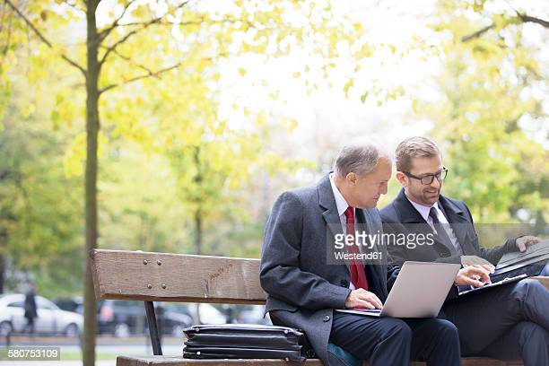 Two businessmen with laptop and documents on park bench