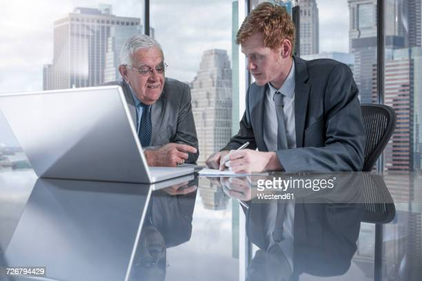 Two businessmen with laptop discussing in office