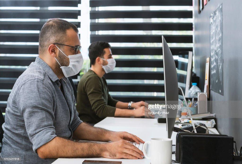 Dos hombres de negocios con máscaras protectoras están trabajando en la oficina : Foto de stock