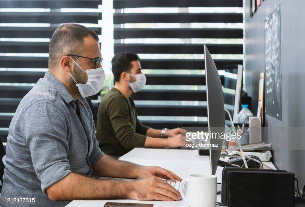 two businessmen with protective face masks are working in the office - protective workwear stock pictures, royalty-free photos & images