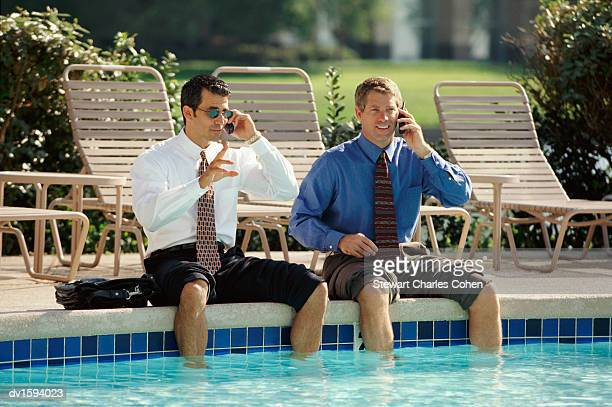 two businessmen with rolled up trousers, sat poolside with their legs in the water, using mobile phones - rolled up pants stock pictures, royalty-free photos & images