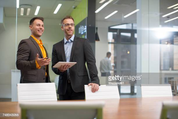 Two businessmen with tablet in office boardroom