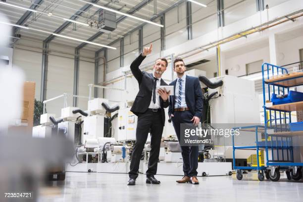 Two businessmen with tablet talking in factory shop floor