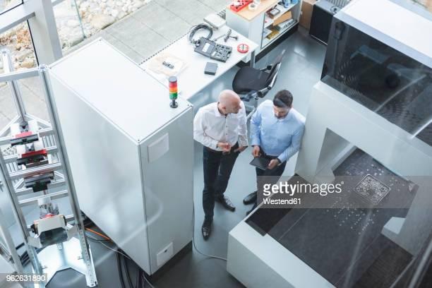 two businessmen with tablet talking in industrial office - blickwinkel der aufnahme stock-fotos und bilder