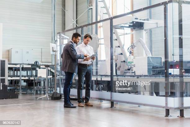 Two businessmen with tablet talking in modern factory