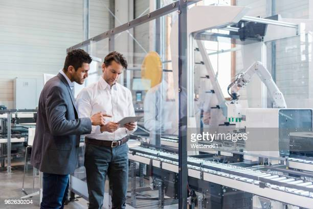 two businessmen with tablet talking in modern factory - automation stock pictures, royalty-free photos & images