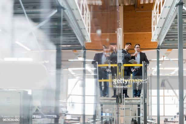 two businessmen with tablet talking in modern factory - halle gebäude stock-fotos und bilder