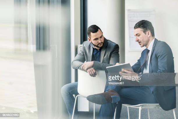 Two businessmen with tablet talking in office at the window