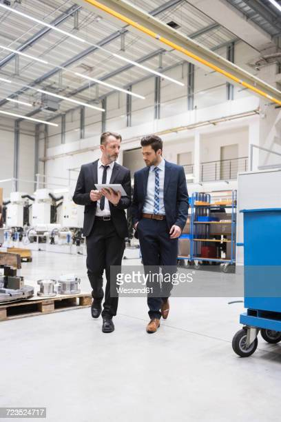 Two businessmen with tablet walking in factory shop floor