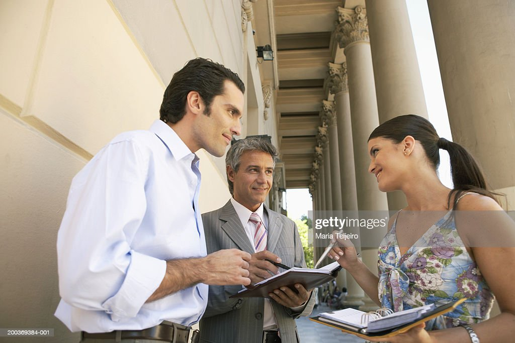 Two businessmen with young woman writing in diary, smiling : Stock Photo