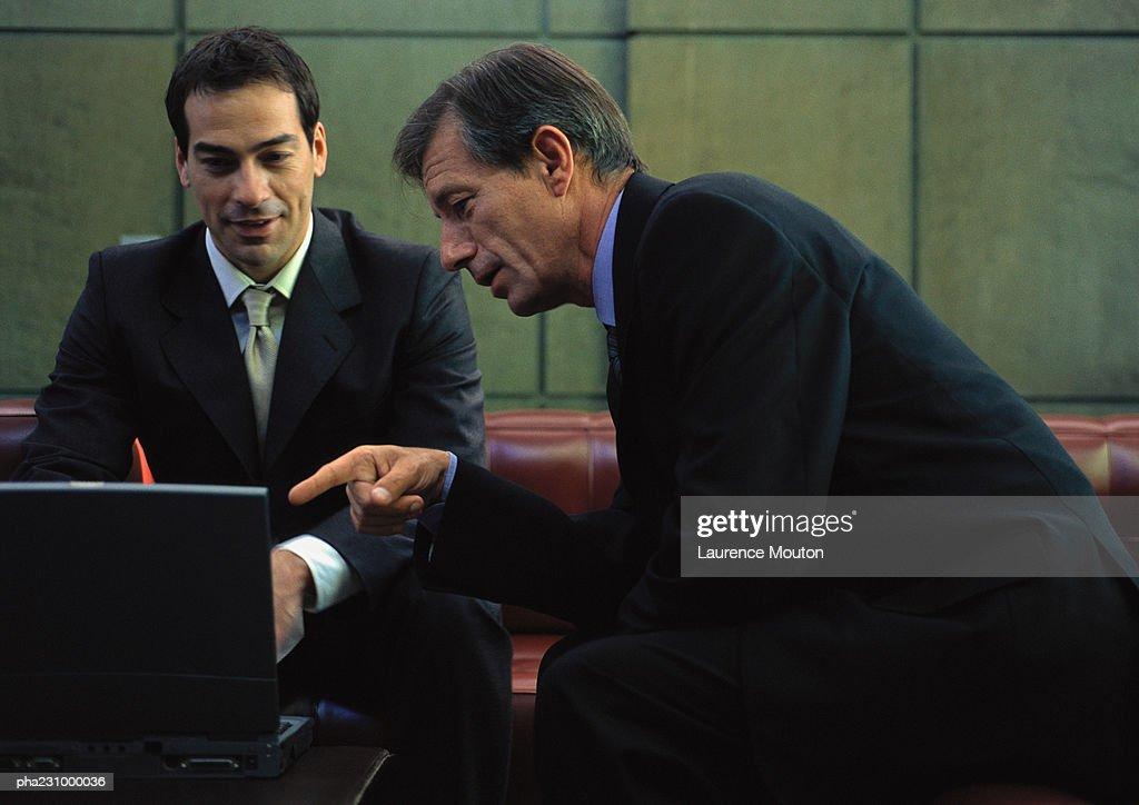 Two businessmen working around laptop computer, portrait : Stockfoto