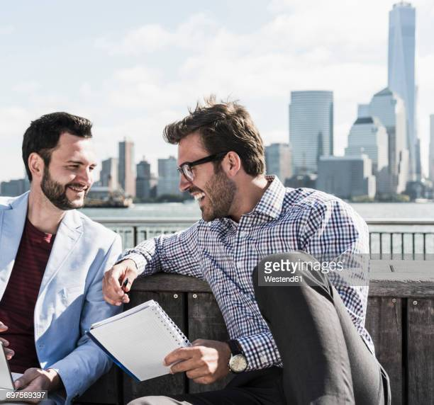 USA, two businessmen working at New Jersey waterfront with view to Manhattan