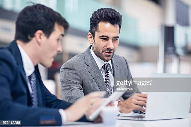 Two businessmen working in the airport