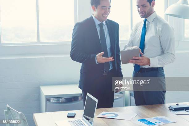 Two businessmen working on a digital tablet.
