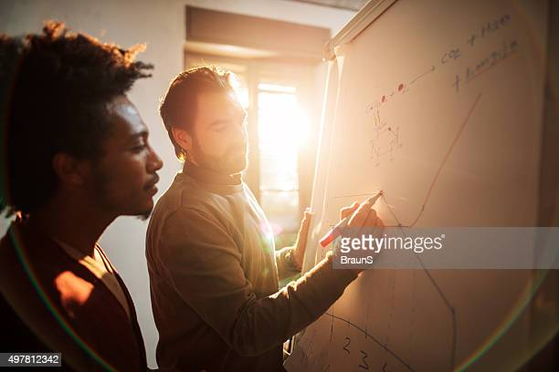 Two businessmen working together on a business graph at office.