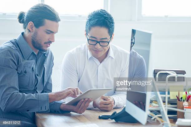 Two businessmen working with a digital tablet.