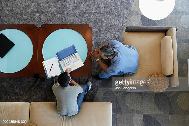 Two businessmen working with laptop, elevated view