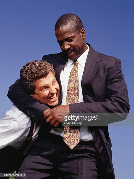 Two businessmen wrestling, one in headlock
