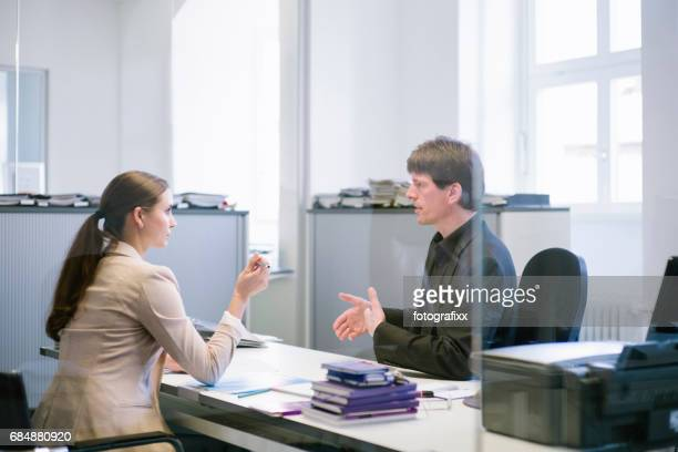 two businesspeople discuss in office, talking, gesturing