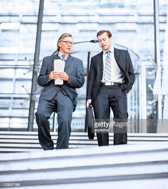 Zwei Geschäftsleute, die Treppe hinunter.