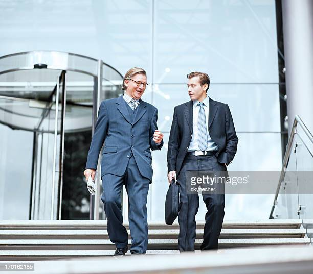 Two businesspeople going down the stairs.
