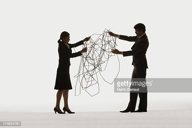 Two businesspeople holding a cable