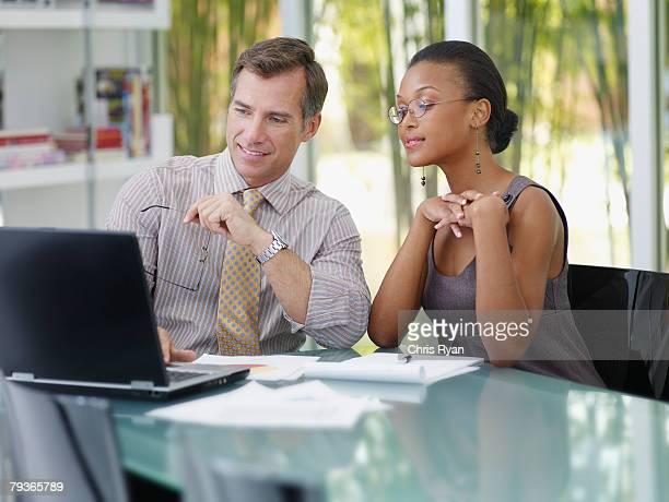 Zwei Geschäftsleute in Büro Blick auf einen laptop
