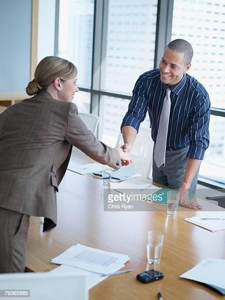 Zwei Geschäftsleute, die Hand schütteln in boardroom