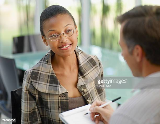 Two businesspeople in boardroom with notepad