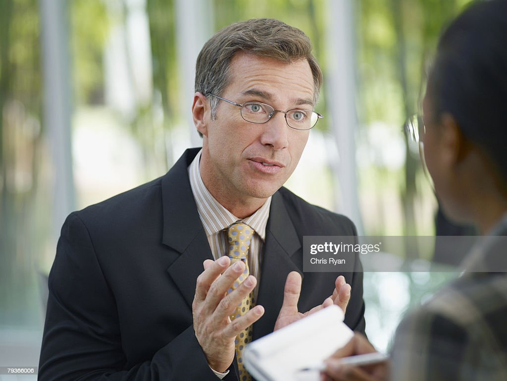 Two businesspeople in boardroom with notepad : Stock Photo