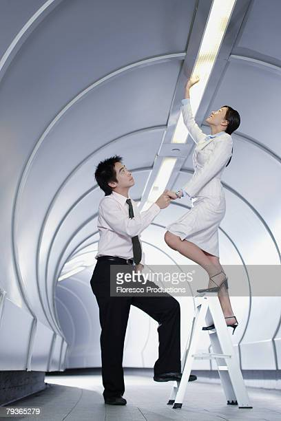 Two businesspeople in corridor changing a light bulb