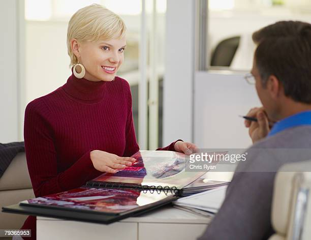 Two businesspeople in office looking at an album