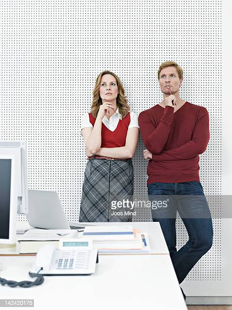 two businesspeople in office, thinking