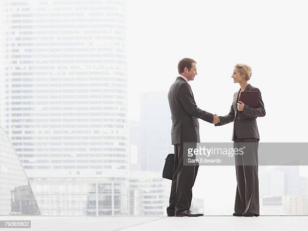two businesspeople outdoors shaking hands at top of staircase - equality stock pictures, royalty-free photos & images