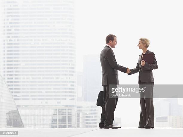 Dos hombres de negocios estrechándose las manos al aire libre en la cima de la escalera