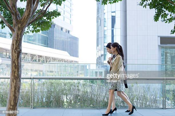 Two businesspeople outdoors walking by building