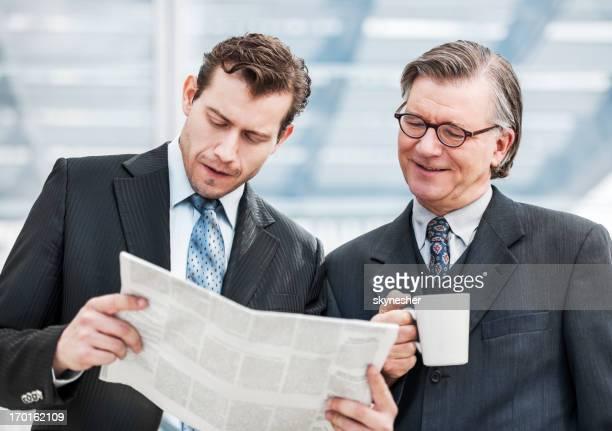 Dois empresários ler nos jornais.