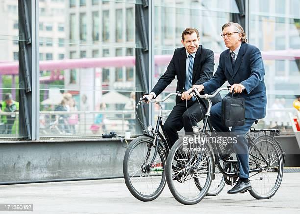 Zwei Geschäftsleute Reiten Fahrräder.