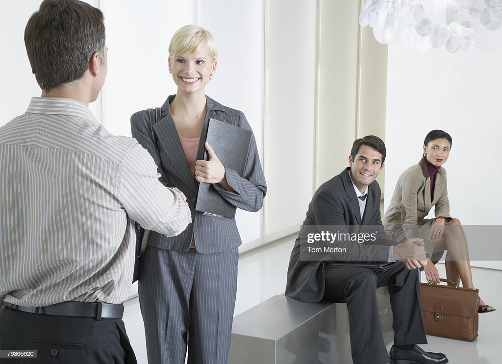 Two businesspeople shaking hands in office lobby with two businesspeople watching : Stock Photo