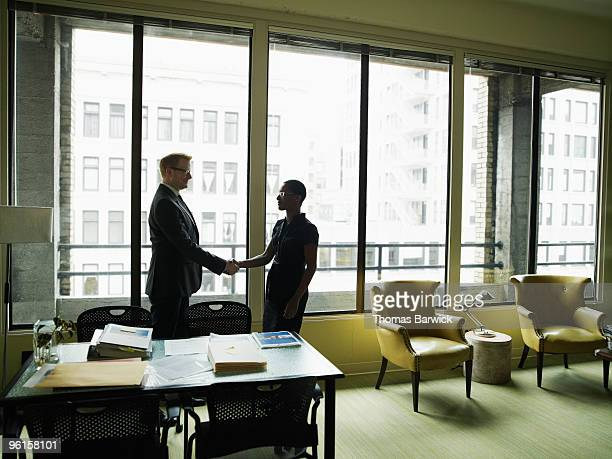 two businesspeople shaking hands in office - leanintogether stock pictures, royalty-free photos & images