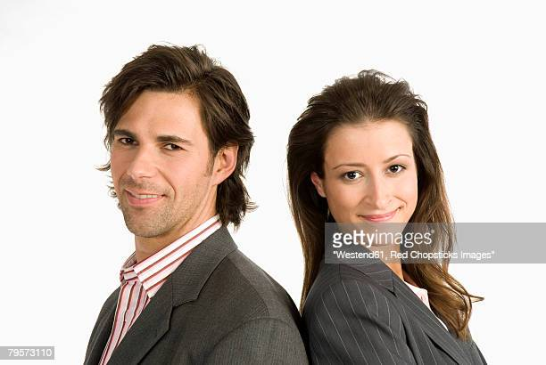 two businesspeople standing back to back - heterosexual couple stock pictures, royalty-free photos & images