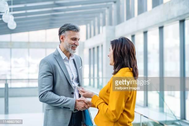 two businesspeople standing in a corridor in an office building, shaking hands. - schütteln stock-fotos und bilder