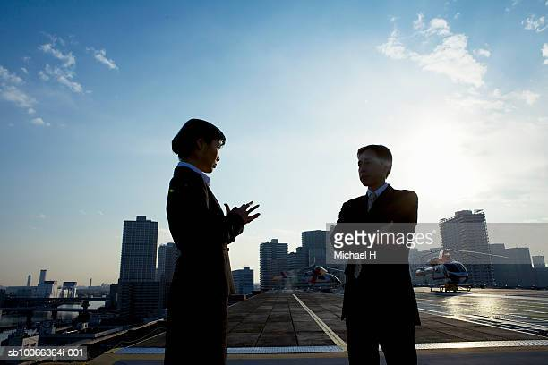 Two businesspeople standing on runway and talking, dusk