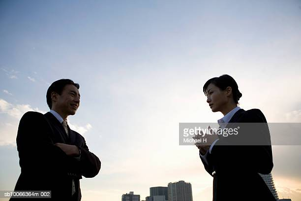 Two businesspeople talking, low angle view