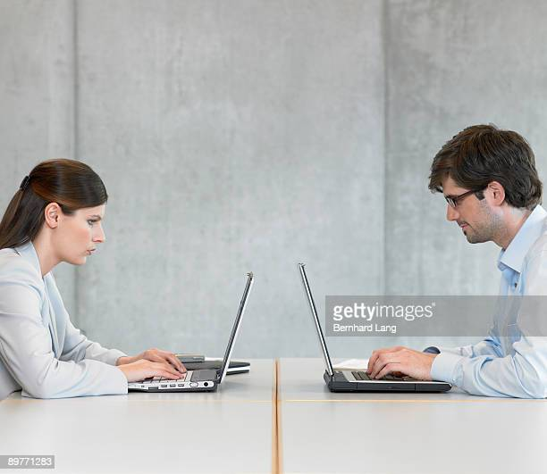 two businesspeople using laptops - face to face stock pictures, royalty-free photos & images