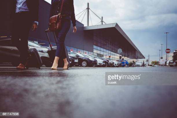two businesspeople walking in airport parking lot - car park stock pictures, royalty-free photos & images