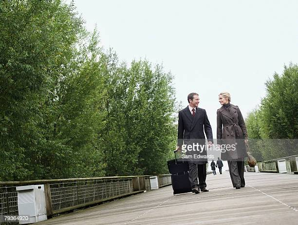 two businesspeople walking on bridge with luggage - heterosexual couple stock pictures, royalty-free photos & images